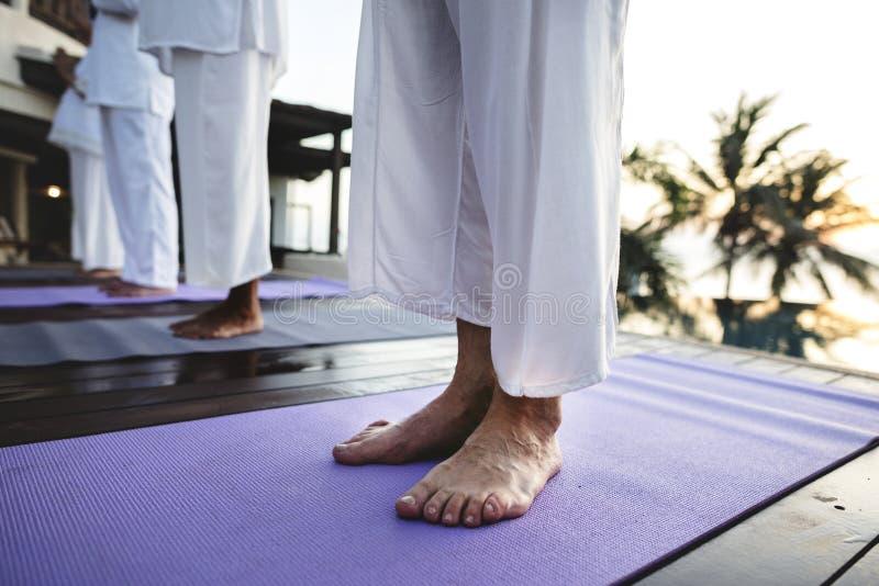 Grupp av pensionärer som öva yoga vid pölen royaltyfri foto