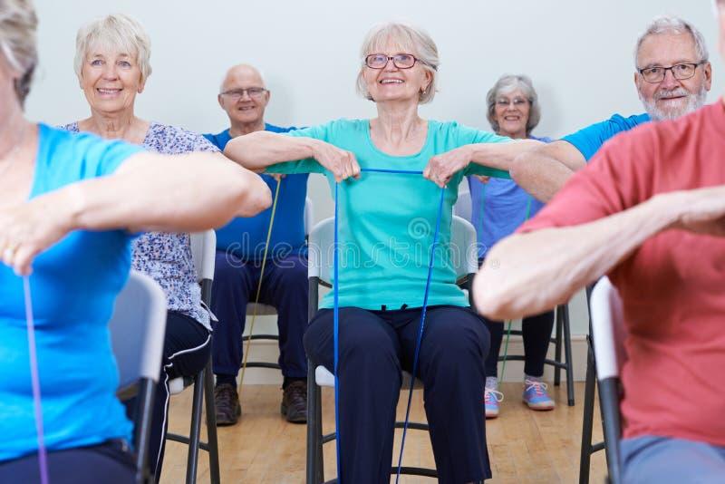 Grupp av pensionärer som använder motståndsmusikband i konditiongrupp royaltyfri fotografi