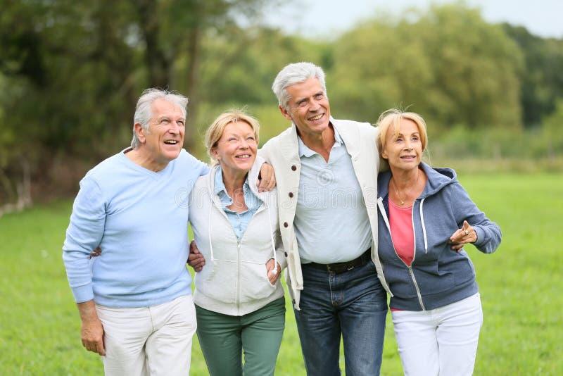 Grupp av pensionärer som går utomhus i natur royaltyfria foton