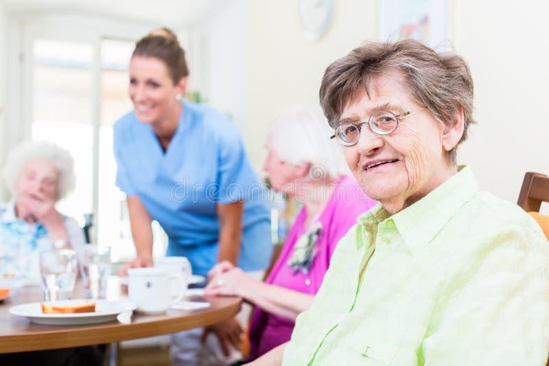 Grupp av pensionärer som har mat i vårdhem royaltyfri bild