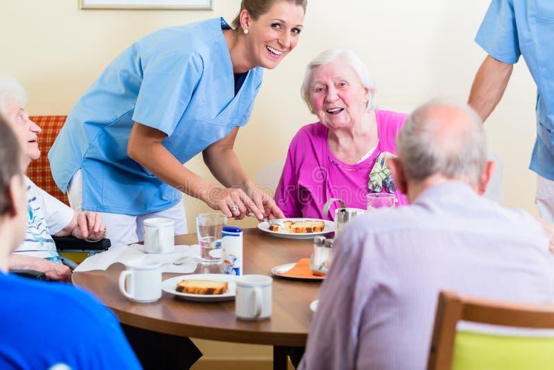 Grupp av pensionärer som har mat i vårdhem arkivbild