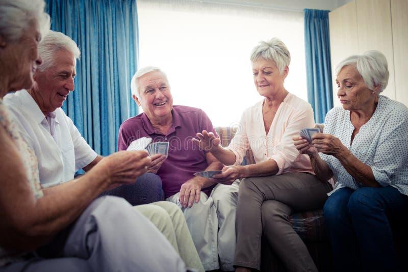Grupp av pensionärer som spelar kort arkivbild