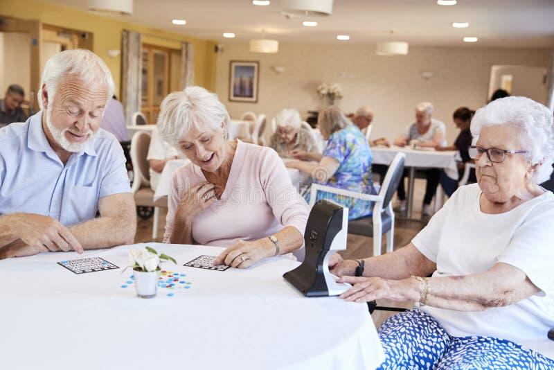 Grupp av pensionärer som spelar leken av bingoen i avgånghem royaltyfria bilder