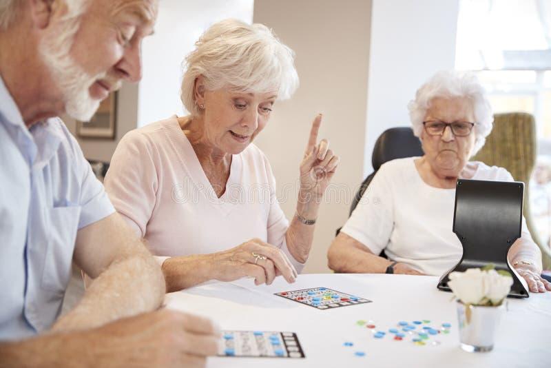 Grupp av pensionärer som spelar leken av bingoen i avgånghem royaltyfri foto