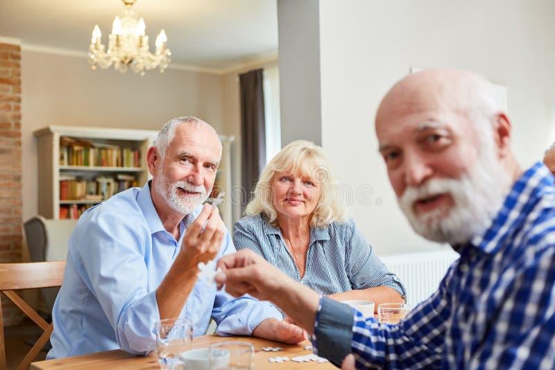 Grupp av pensionärer som spelar pusselleken tillsammans arkivfoto