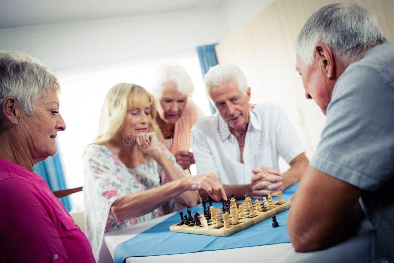 Grupp av pensionärer som spelar schack fotografering för bildbyråer