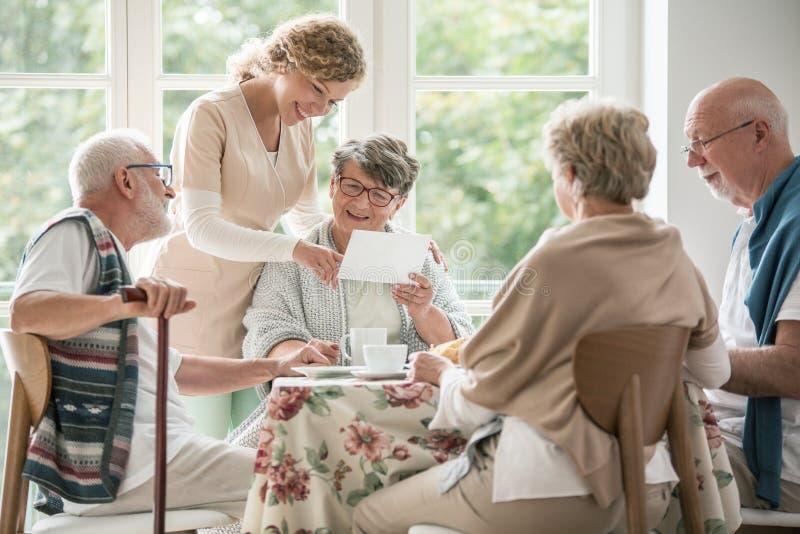 Grupp av pensionärer som tillsammans dricker te Sjuksköterskan visar ett foto till hennes kvinnliga patient fotografering för bildbyråer