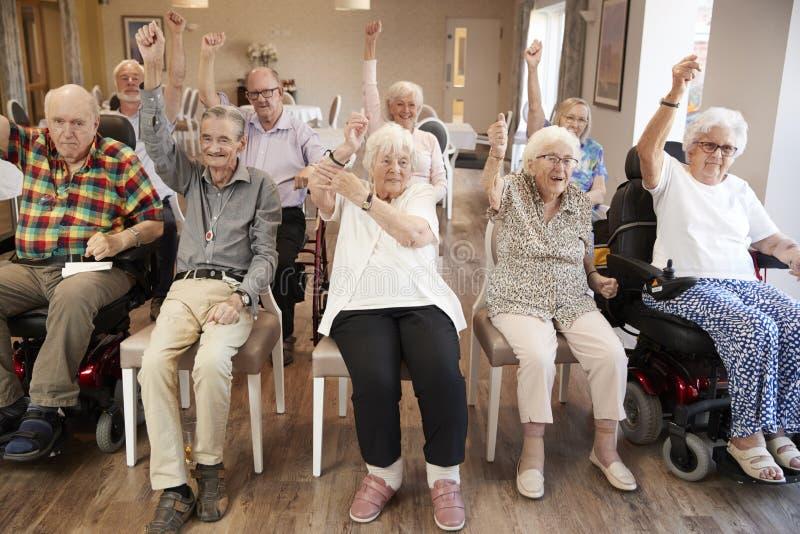 Grupp av pensionärer som tycker om konditiongrupp i avgånghem royaltyfria foton