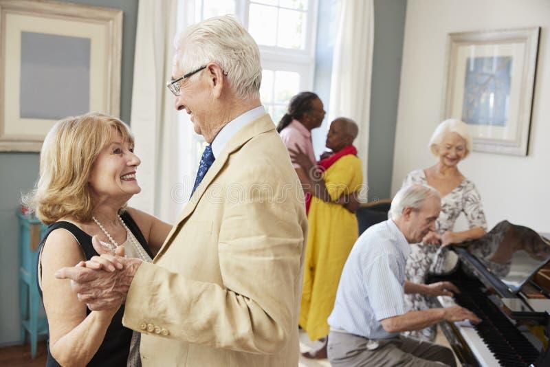 Grupp av pensionärer som tycker om som tillsammans dansar klubban royaltyfri fotografi