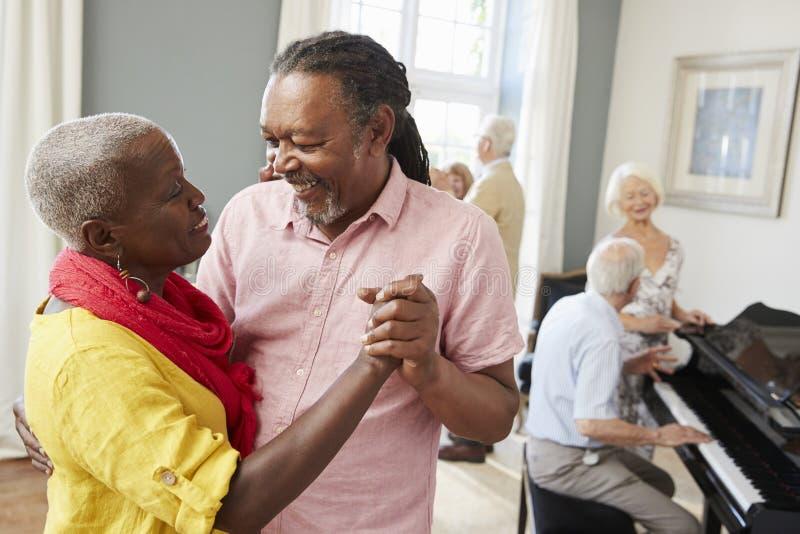 Grupp av pensionärer som tycker om som tillsammans dansar klubban royaltyfri foto