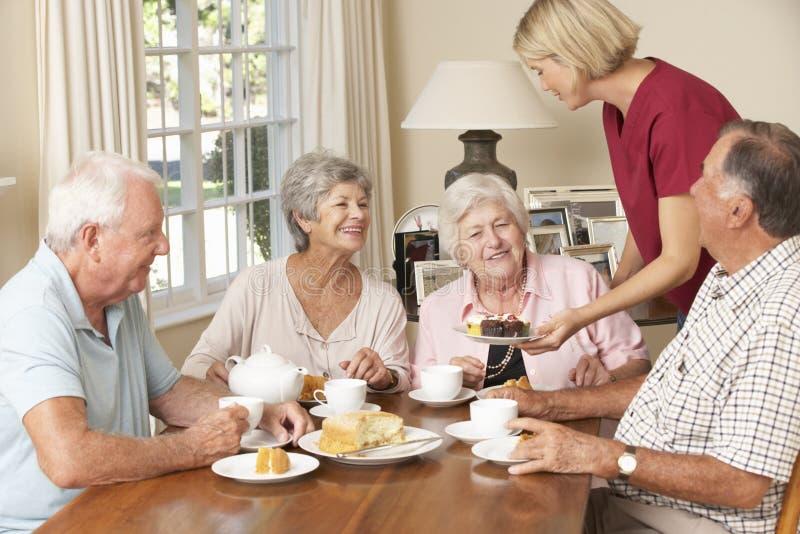 Grupp av pensionärpar som tillsammans tycker om eftermiddagte hemma med hemhjälp arkivfoton