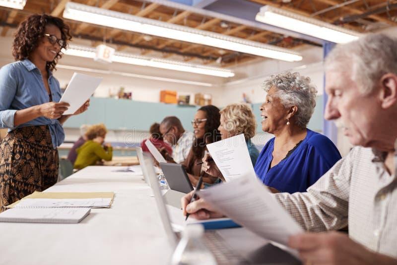 Grupp av pensionerade pensionärer som deltar i DEN grupp i gemenskapmitt med läraren royaltyfri bild