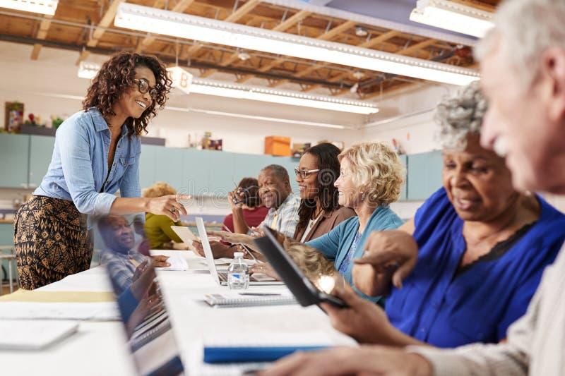 Grupp av pensionerade pensionärer som deltar i DEN grupp i gemenskapmitt med läraren royaltyfri fotografi
