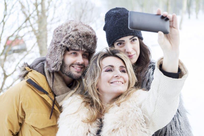 Grupp av personen som tar selfie i vinterskog royaltyfri fotografi