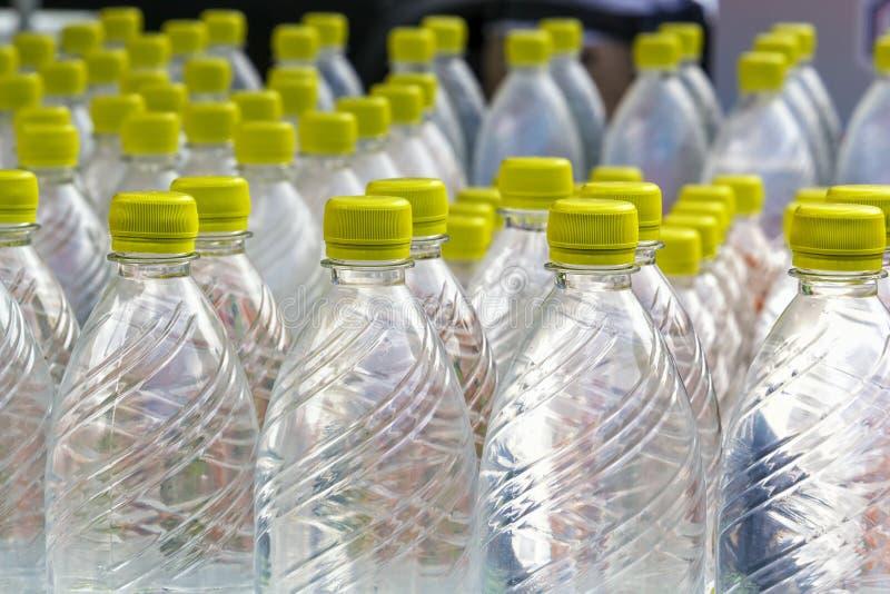 Grupp av plast- flaskor med vattenställningen i rad arkivfoton