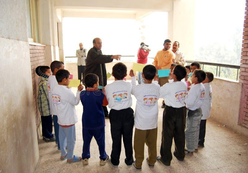 Grupp av pojkar i cirklar som får anvisningar från lärare arkivfoto