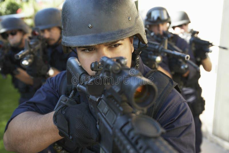 Grupp av poliser som siktar med vapen royaltyfria bilder