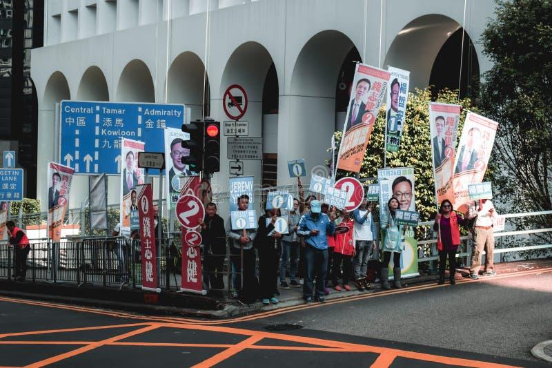 Grupp av politiska supportrar som marscherar gatorna av Hong Kong för att stötta deras kandidat för val royaltyfri bild