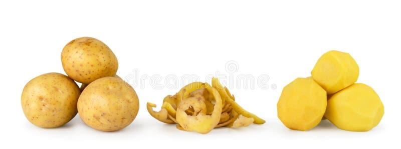Grupp av potatisar, potatispeels och skalade potatisar tätt upp på en vit bakgrund arkivfoto