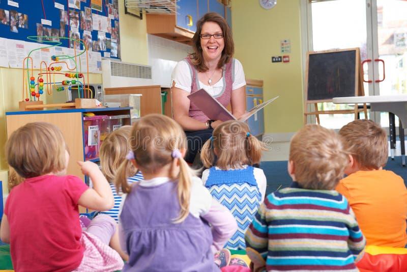 Grupp av Pre skolbarn som lyssnar till läraren Reading Story royaltyfria bilder