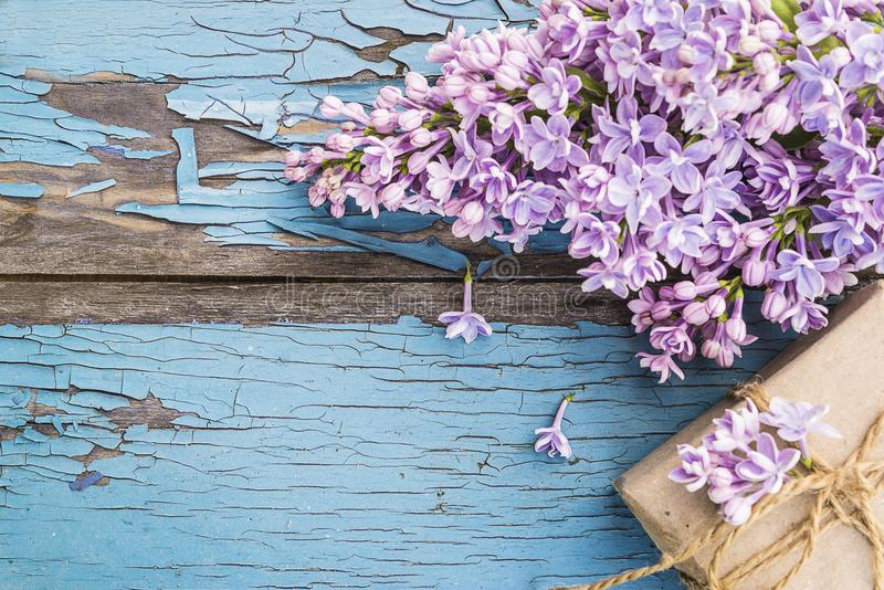 Grupp av purpurfärgade lilor och handen - gjord gåvaask arkivbild