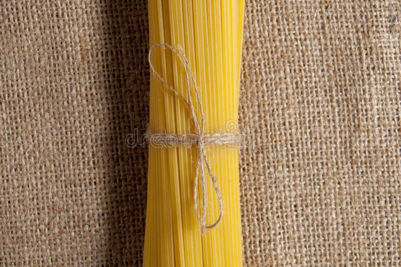 Grupp av rå spagetti som binds med repet på säckväv I mitten av bilden Top beskådar royaltyfria bilder