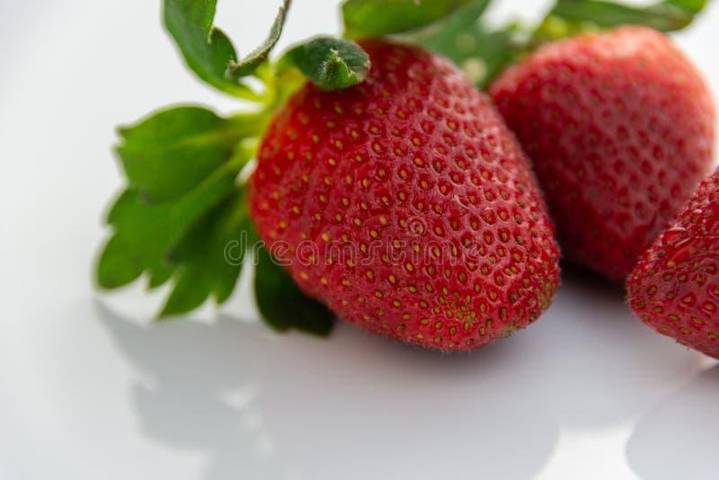 Grupp av röda jordgubbar med isolerade gröna sidor arkivfoton