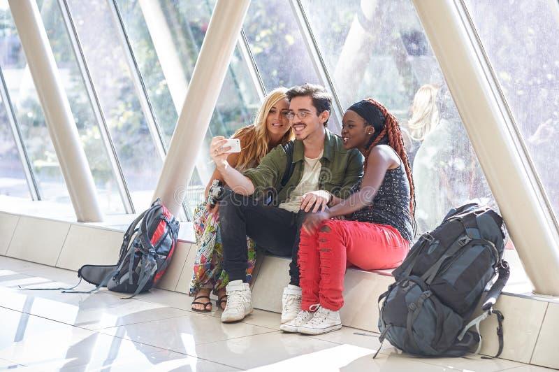 Grupp av resande vänner som tar selfies med den smarta telefonen royaltyfria bilder