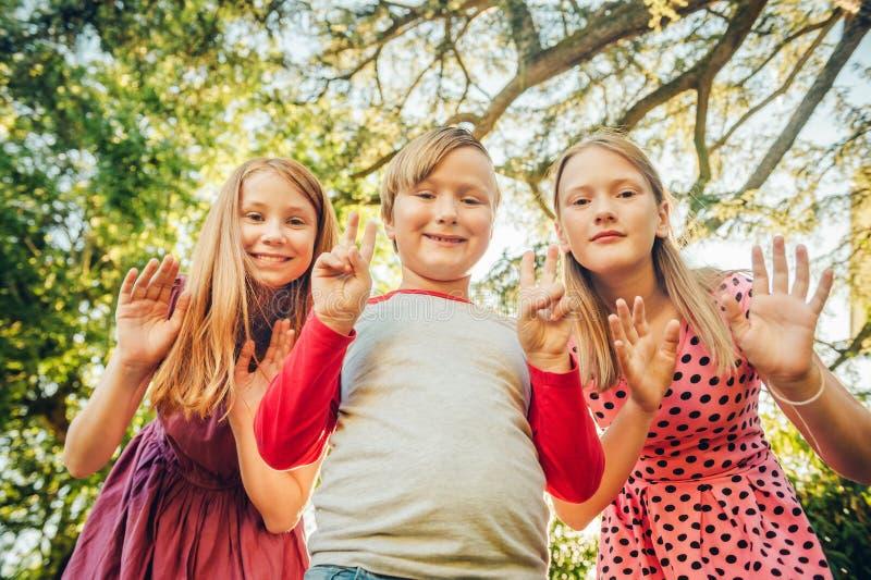 Grupp av 3 roliga ungar som tillsammans utanför spelar fotografering för bildbyråer