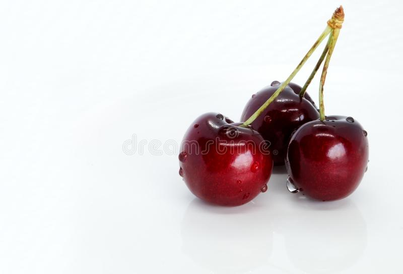 Grupp av söta körsbär på en vit platta arkivfoto
