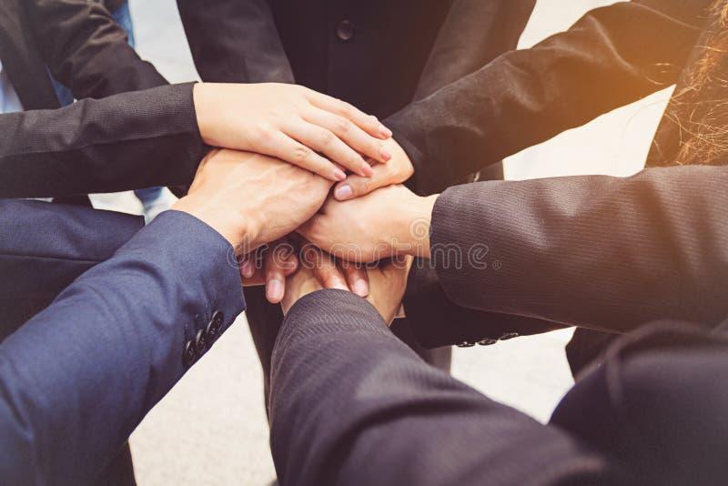 Grupp av sammanfogande händer för affärsfolk för begreppsdockor för bakgrund svart färgrikt arbete för lag royaltyfri bild