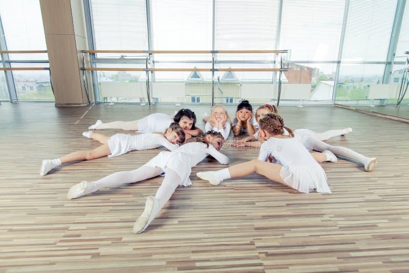 Grupp av sju lilla ballerina som sitter på golvet De är royaltyfria bilder