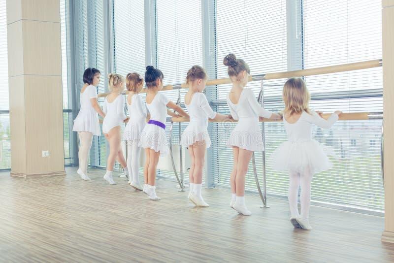 Grupp av sju lilla ballerina som står, i rad och övning arkivfoton