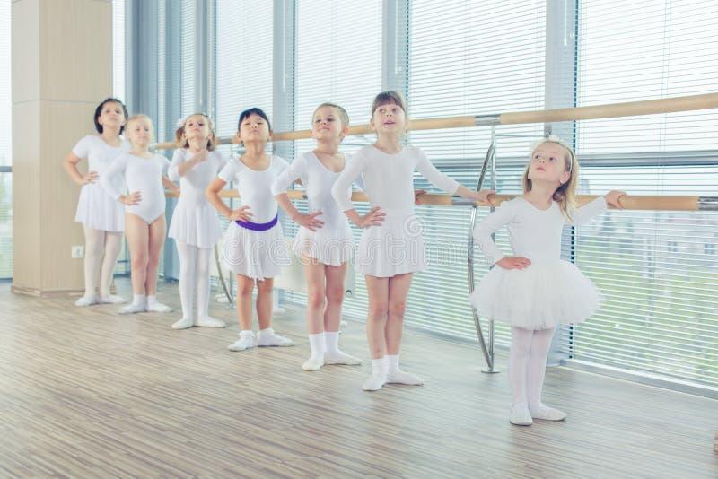 Grupp av sju lilla ballerina som står, i rad och övning royaltyfria bilder