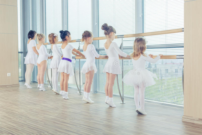Grupp av sju lilla ballerina som står, i rad och övning royaltyfri fotografi