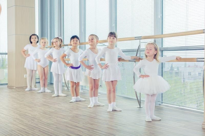 Grupp av sju lilla ballerina som står, i rad och övning royaltyfria foton
