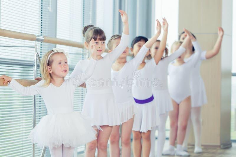 Grupp av sju lilla ballerina som står i rad och praktiserande balett genom att använda pinnen på väggen royaltyfria foton