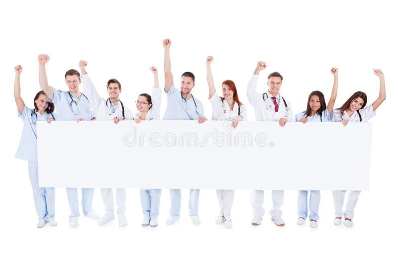 Grupp av sjukvårdpersonaler som rymmer ett baner arkivbild