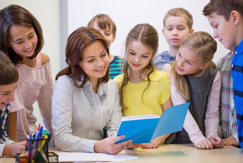 Grupp av skolaungar med läraren i klassrum arkivbilder