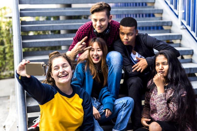 Grupp av skolavänner som har roligt och tar en selfie arkivbilder