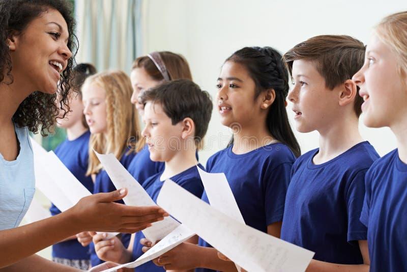 Grupp av skolbarn med läraren Singing In Choir arkivbilder