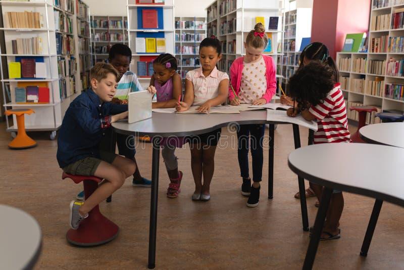 Grupp av skolbarn som tillsammans studerar på tabellen i skolaarkiv royaltyfri fotografi