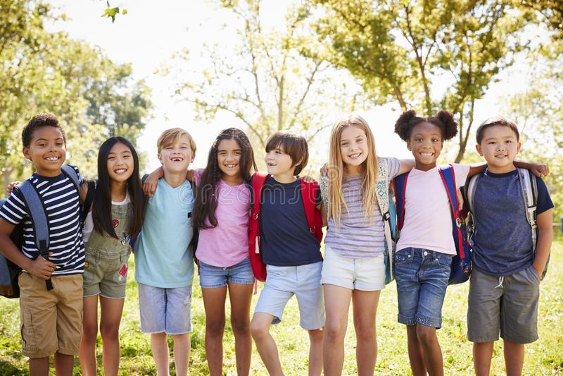 Grupp av skolbarnställningen som i rad omfamnar utomhus fotografering för bildbyråer