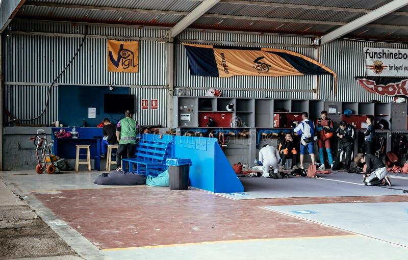 Grupp av skydivers som förbereder sig för att hoppa händelse som kontrollerar utrustning arkivbild