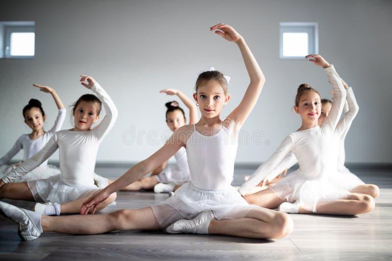 Grupp av små ballerinaflickor som gör övningar i dansskola royaltyfri foto