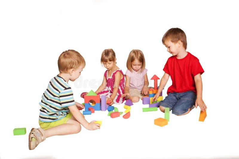 Grupp av små barn som spelar och bygger arkivbild
