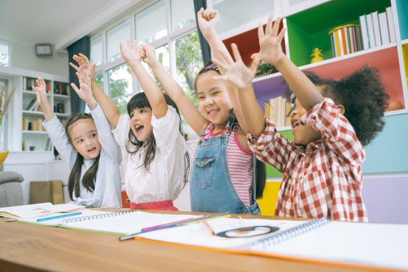 Grupp av små förskole- ungehänder upp i grupp stående av begreppet för barnmångfaldutbildning royaltyfria foton