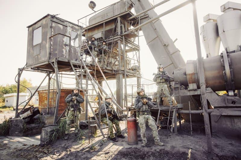 Grupp av soldater som bevakar växten arkivfoton