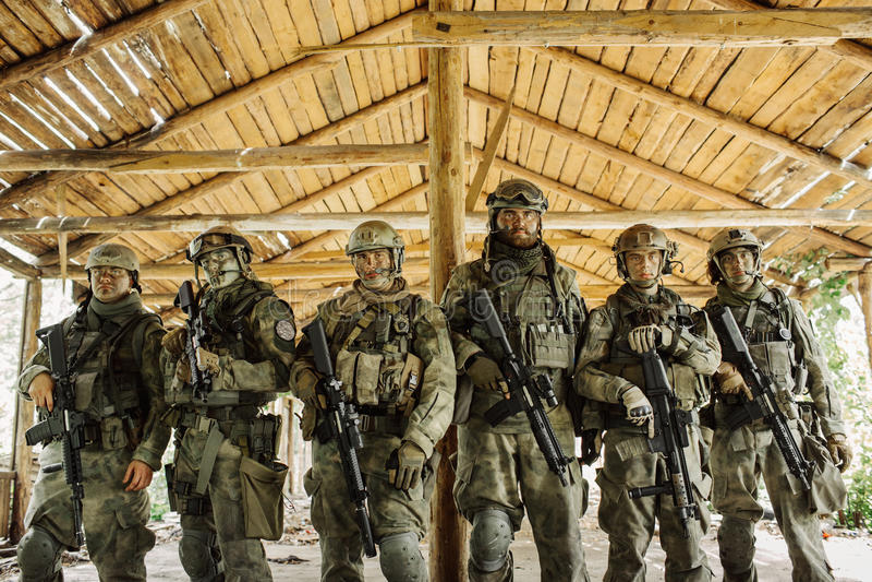 Grupp av soldater som står och ser kameran royaltyfri bild