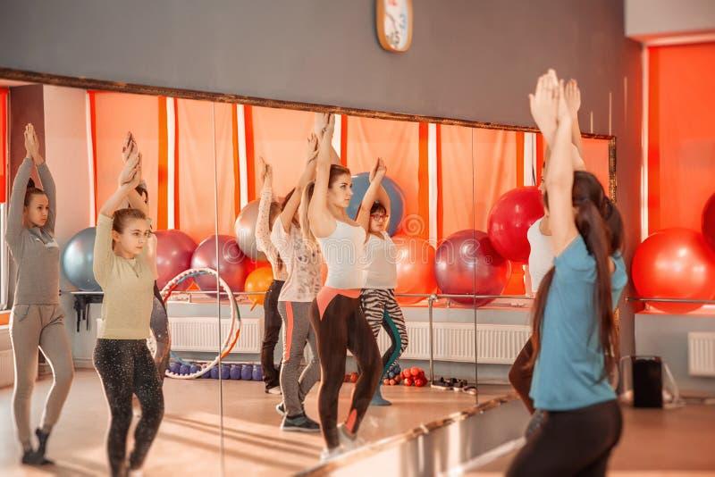 Grupp av sportive av tonårs- flickor som övar i idrottshallen Sunt livsstilbegrepp för barn arkivfoto